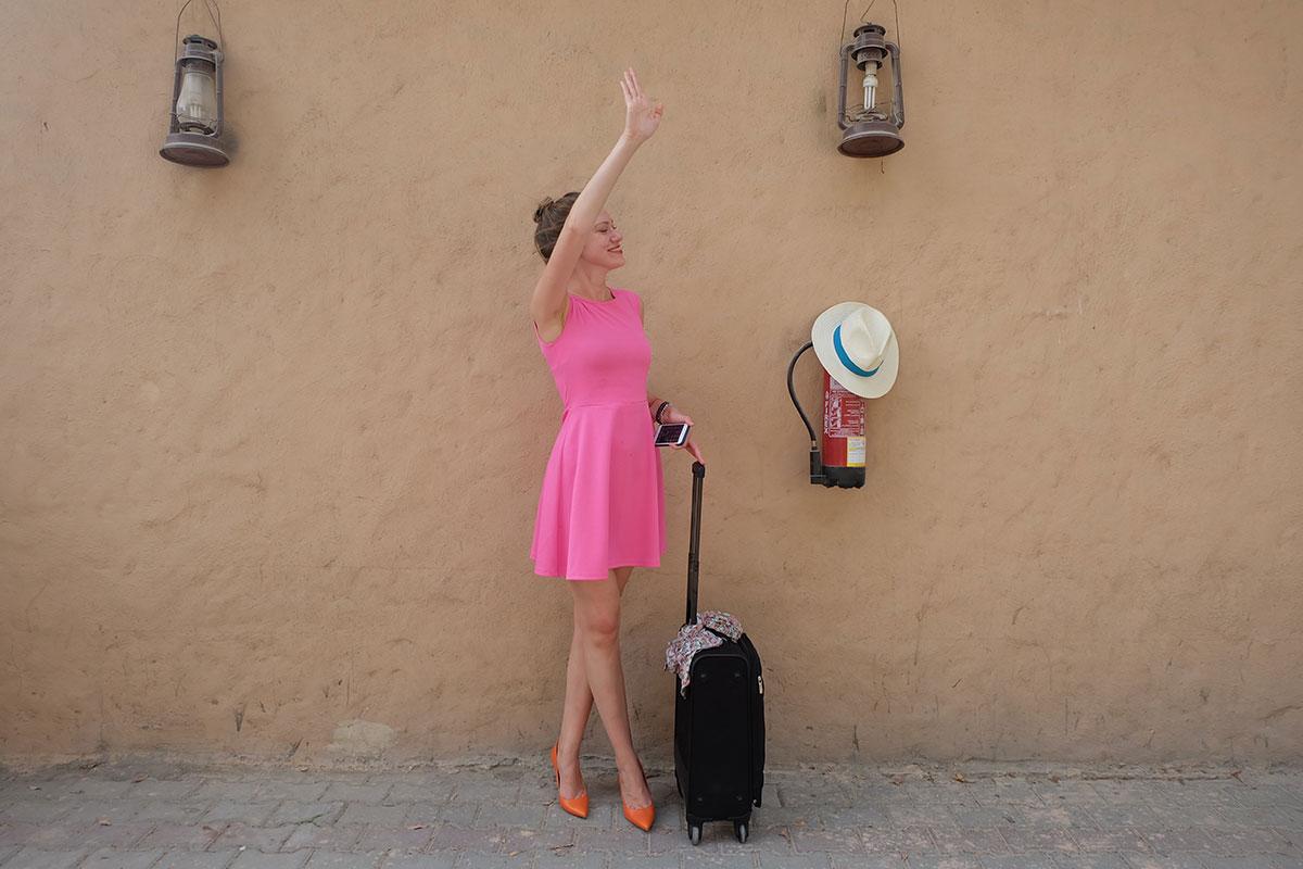 Frau in rosa Kleid winkt