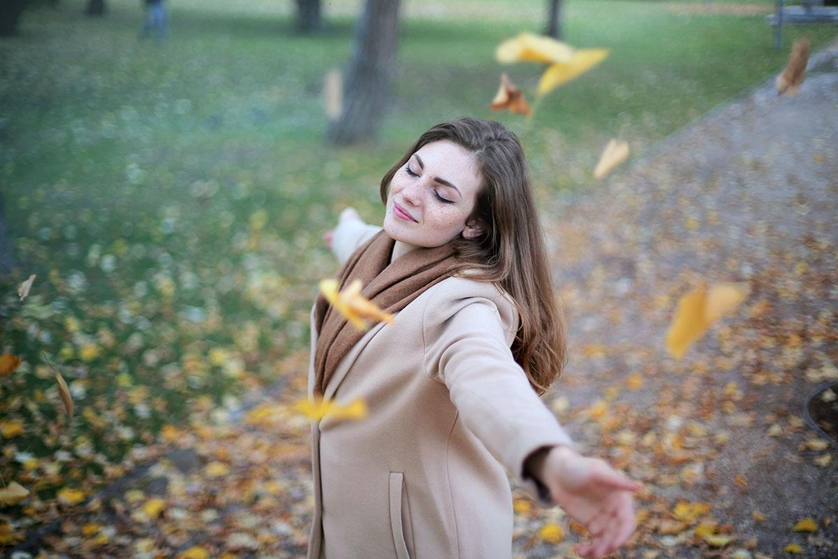 Frau mit herbstlichen Blättern